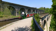 Canal boat being passed by a train on the Llangollen canal Stock Footage