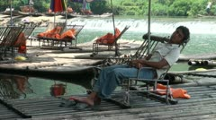 Tour guide takes a nap at rafting area Stock Footage