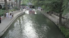 Stock Footage - River Boat Passes Under Bridge - Tourists Wave - Overhead shot Stock Footage