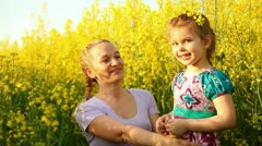 Mom and daughter in a field of flowers. They laughed very much Stock Footage