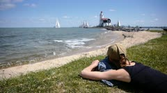 Girl watching lighthouse and sailing boat in sunny landscape Stock Footage