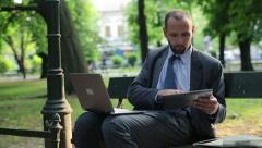 Businessman working on tablet computer and laptop in the city park HD - stock footage