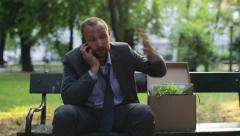 Just fired angry businessman talking on cellphone in the city park HD Stock Footage