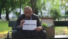 """Just fired sad businessman holding paper sheet with """"UNEMPLOYED"""" sign HD Stock Footage"""