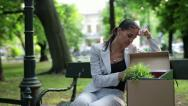 Just fired, unemployed sad young businesswoman sitting in the park HD Stock Footage
