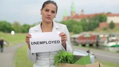 "Just fired sad businesswoman holding paper sheet with ""UNEMPLOYED"" sign HD - stock footage"