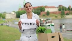 "Happy jobless businesswoman holding paper sheet with ""HIRE ME"" sign HD Stock Footage"