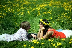 Mother with daughter lying on meadow and chatting together Stock Footage