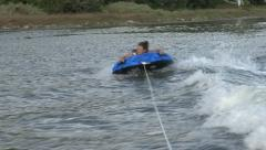 Girl being pulled on tube by speed boat Stock Footage