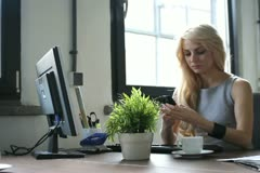 Businesswoman with cellphone sending a text message, dolly shot - stock footage