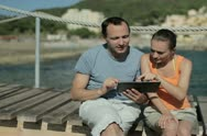 Young couple with digital tablet sitting by the sea, tracking shot NTSC Stock Footage