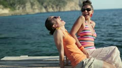 Portrait of two happy laughing girls sitting by the sea, tracking shot HD - stock footage