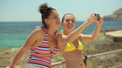 Two female friends on summer holidays taking photo with cellphone  HD Stock Footage
