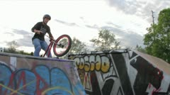 BMX bike rider does tricks in a skatepark - stock footage