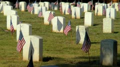 Flags on unknown soldier graves and others in military cemetery at sunrise - stock footage