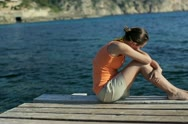 Sad young woman sitting on pier by the sea, tracking shot NTSC Stock Footage