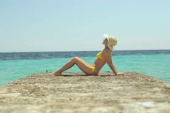 Sexy young woman in bikini and summer hat sitting on stone pier NTSC Stock Footage