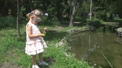 Child Trowing Flowers in a Pond Stock Footage