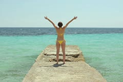 Woman with wide open arms standing by the tropical sea NTSC Stock Footage