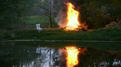 Spring evening fire in the farm near pond Stock Footage