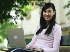 Young happy girl with laptop in the city park NTSC - stock footage