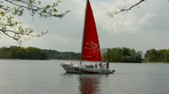Yacht with red sail sailing on the lake Stock Footage