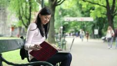 Young student working on laptop and writing notes in city park HD - stock footage