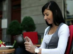 Young girl drinking cocktail and using tablet computer in cafe NTSC Stock Footage
