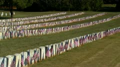 Military cemetery with flags on graves at sunrise - stock footage