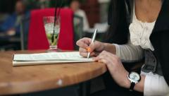 Female student hands writing notes in cafe HD Stock Footage