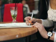 Female student hands writing notes in cafe NTSC Stock Footage