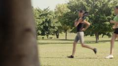 Sport with two young women jogging in city park - stock footage