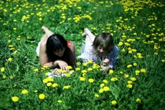 Mother and daughter lying on meadow full of sow-thistle and reading book Stock Footage