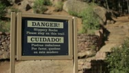 Stock Video Footage of Danger! Slippery Rocks Sign, Cuidado