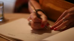 Woman writing in guest book at wedding - stock footage