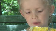 Mother Gives to her Child to Eat a Boiled Corn on a Bench in Park, Children Stock Footage