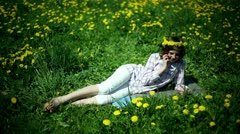 Teenager girl lying on meadow full of sow-thistle and talking on cellphone Stock Footage
