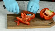 Hands with azure glove cutting red pepper Stock Footage