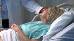 Physician demonstrates bedside manner to patient - stock footage