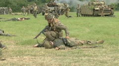 American soldier checks dead soldiers on the battlefield after combat Stock Footage