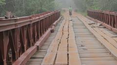 Woman walking across bridge Stock Footage