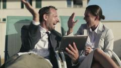 Successful business couple with tablet computer lying on sunbeds HD Stock Footage