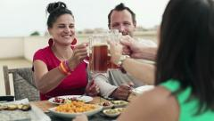 Young happy friends drinking beer during lunch HD Stock Footage