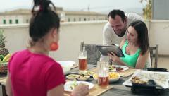 Young friends with tablet computer by the table full of food HD Stock Footage