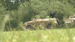 German armoured car and troops on the battlefield - stock footage