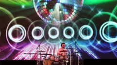 Drummer plays in front of large LED screen Stock Footage