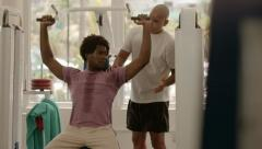 Personal trainer helping man working out in fitness gym Stock Footage