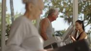 Trainer helping old man and woman exercising in fitness gym Stock Footage