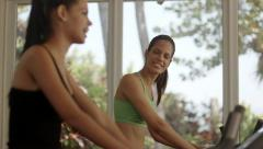 Pretty young girls training on fitness bikes in gym Stock Footage