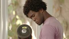 Young black man taking weights from rack in gym - stock footage